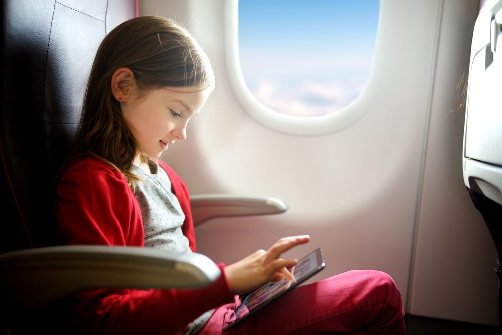 Girl on plane playing with ipad