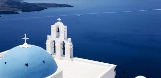 a blue domed church overlooking the mediterranean in satorini