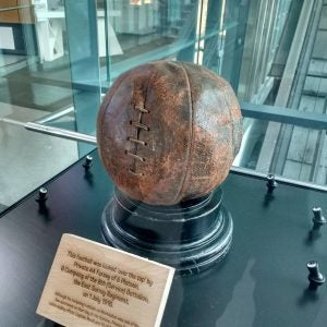 an old football in a display case at the national football museum manchester