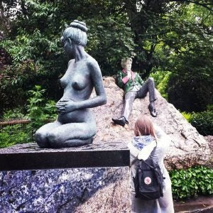a woman taking a photo of the oscar wilde statue dublin