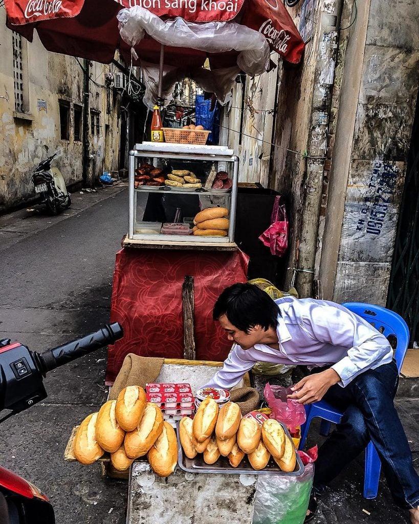a vendor selling bahn mi in hanoi