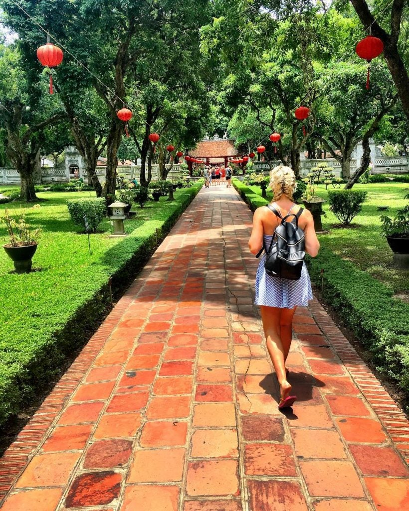 a woman walking to the temple of literature hanoi vietnam