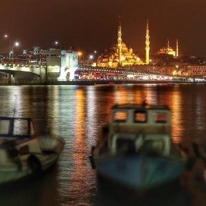 fishing boats tied on the bosphorus with the blue mosque in the background