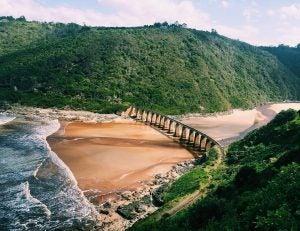 a bridge over a sandy beach along the garden route south africa