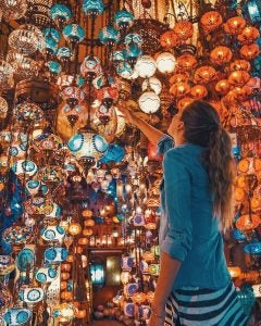 a woman looking at lamps in the grand bazaar istanbul