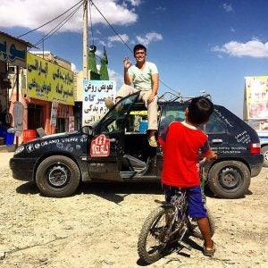 a man sits on his rally car during the mongol rally