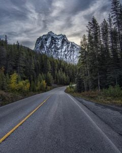 a narrow highway running through the rocky mountains