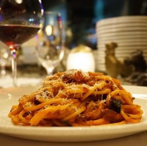 tourists eat bucatini alla amatriciana in rome italy