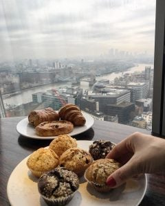 a woman enjoys cupcakes with the london skyline in the background at aquashard