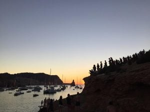 a crowd watches the sunset at benirras beach
