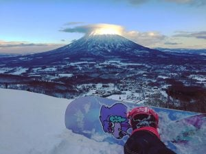 a snowboarder stops and admires the view of the village in hokkaido japan