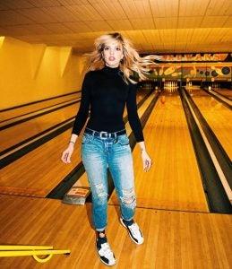 a woman throws a ball at rowan's bowling alley london