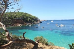 boats anchored in the harbour at ses salines ibiza, best beaches of the balearic islands
