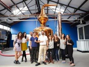 a gin tour group takes a photo at a distillery in london