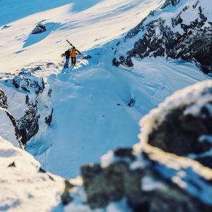 two snowboarders examine a slope in wanaka new zealand