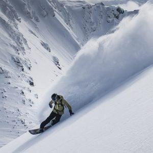 a snowboarder carves a steep slope and sprays powder in whistler canada