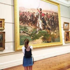 a girl looks at a painting at the nsw art gallery