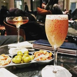 a bellini and olive and cracker spread at the american bar savoy london