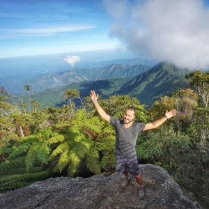 a man celebrates climbing to the top of el pico turquino cuba