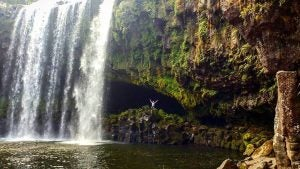 a man stands under a waterfall at the bay of islands