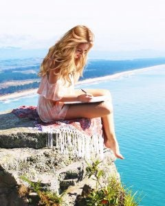 a model writes sitting on a cliff edge at mount maunganui