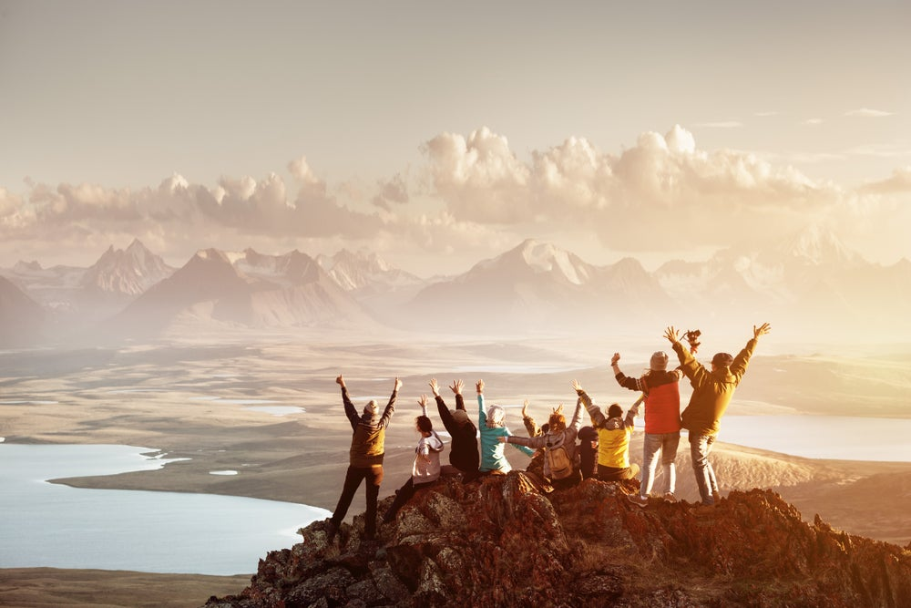 group of people on the mountaintop looking at the panorama with mountains and lakes